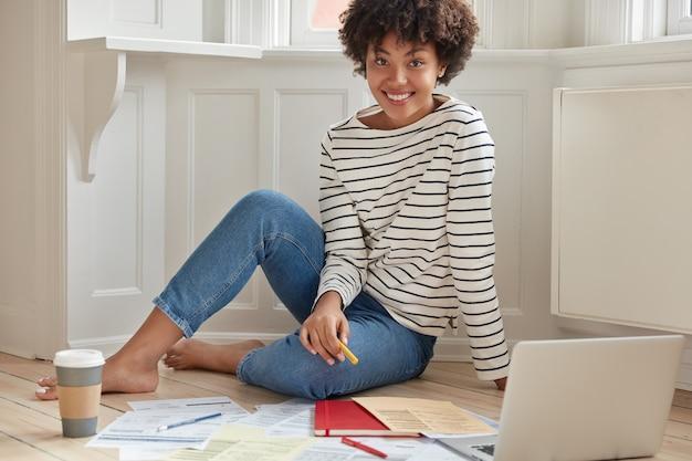 Szczęśliwy afroamerykanin przygotowuje prezentację do pracy szkoleniowej, przeszukuje informacje na komputerze przenośnym