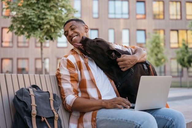 Szczęśliwy afroamerykanin przytulający się z uroczą koncepcją najlepszych przyjaciół z psem