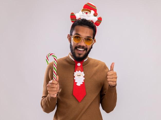 Szczęśliwy afroamerykanin w brązowym swetrze i obręczy mikołaja na głowie z zabawnym czerwonym krawatem trzyma laskę cukrową patrząc na kamery uśmiechnięty wesoło, pokazując kciuki stojąc na białym tle