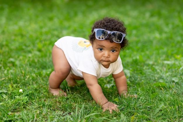 Szczęśliwy afroamerykański chłopczyk na zielonym trawniku latem w okularach pełzających