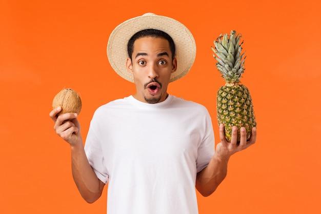 Szczęśliwy afroamerykański chłopiec trzyma kokos i ananasa
