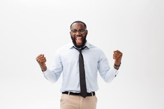 Szczęśliwy afrykański biznesmen jest ubranym korporacyjną szarą koszula i czarnego krawat uderza pięścią powietrze