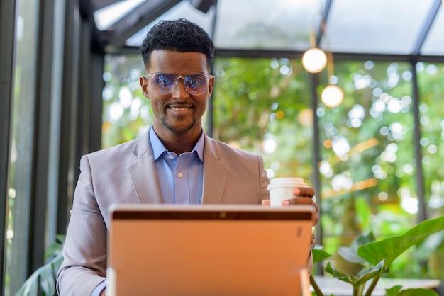 Szczęśliwy afrykański biznesmen w kawiarni przy użyciu laptopa i trzymając filiżankę kawy