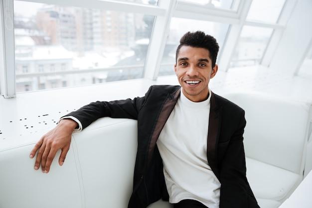 Szczęśliwy afrykański biznesowy mężczyzna w czarnym garniturze, siedzący na kanapie w biurze i patrzący na kamerę
