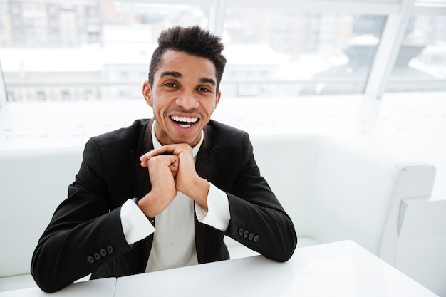 Szczęśliwy afrykański biznesowy mężczyzna w czarnym garniturze siedzi przy stole z rękami blisko twarzy w biurze i patrząc na kamerę