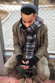 Szczęśliwy afrykański mężczyzna siedzi smartphone outdoors i używa w jesieni