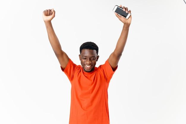 Szczęśliwy afrykański mężczyzna w pomarańczowym t-shirt pozuje