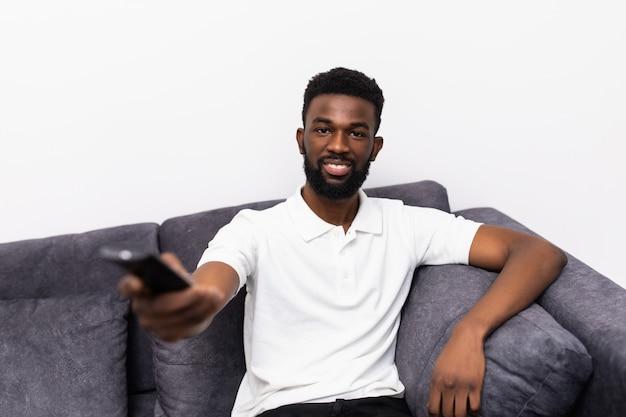 Szczęśliwy afrykański młody człowiek oglądając telewizję na kanapie w domu