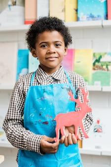 Szczęśliwy afrykański uczeń w niebieskim fartuchu trzymając ręcznie robione jelenie stojąc w klasie przed kamerą