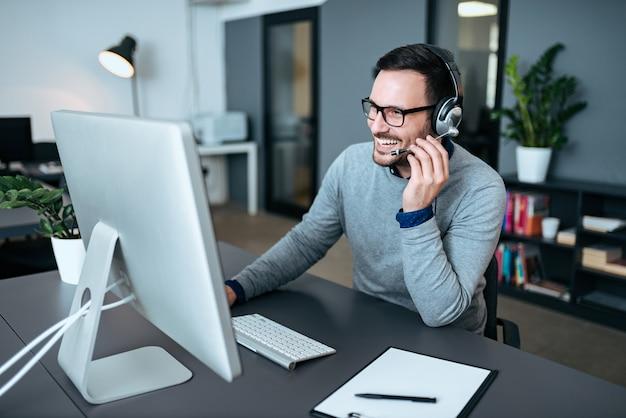 Szczęśliwy agent rozmawia ze swoimi klientami w centrum wsparcia.