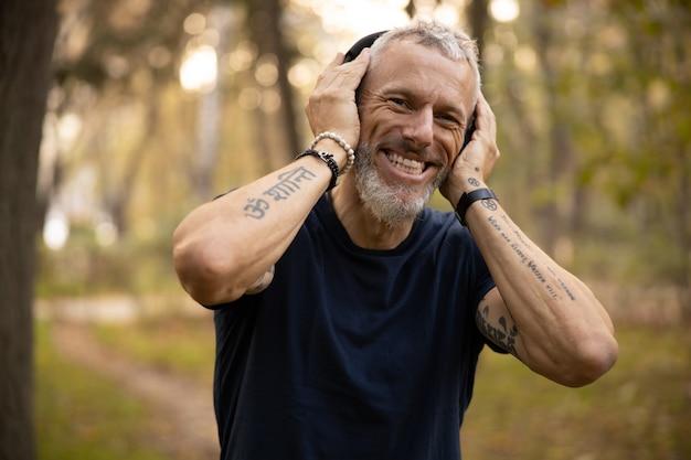 Szczęśliwy aktywny mężczyzna biegający w parku