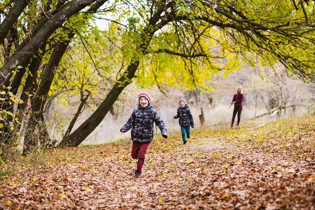 Szczęśliwy aktywny rodzinny weekend w jesiennym lesie z kolorowymi liśćmi. matka bawi się z preteen chłopcami na świeżym powietrzu
