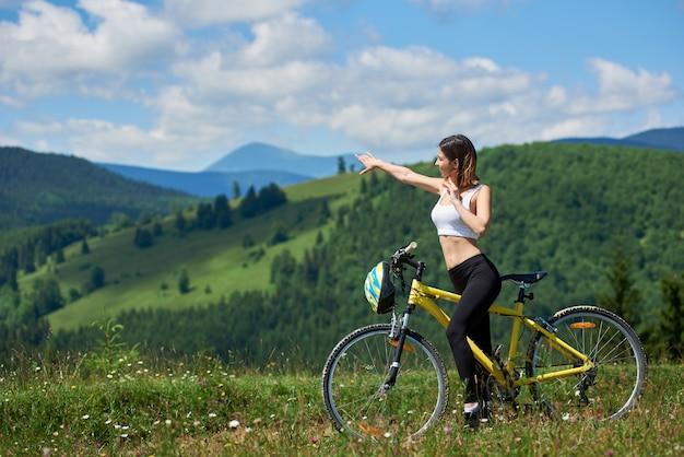 Szczęśliwy aktywny żeński cyklista jedzie na żółtym bicyklu na wiejskim śladzie w górach, wskazuje przy coś w odległości na letnim dniu. góry, lasy i błękitne niebo na tło zamazane pole
