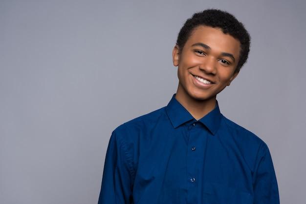 Szczęśliwy amerykanin afrykańskiego pochodzenia nastolatek w drelichowej koszula.