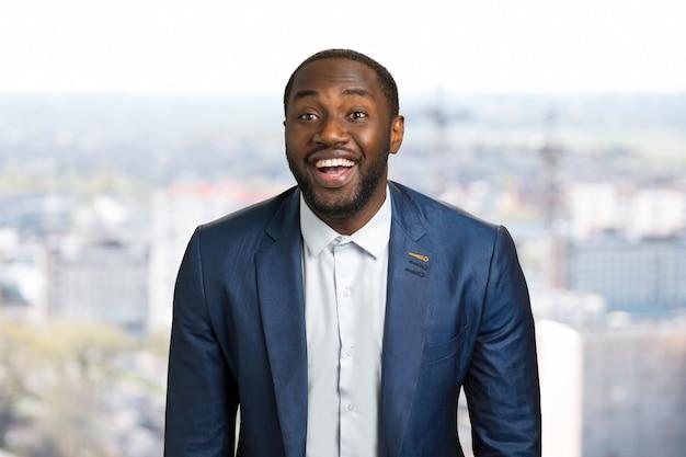 Szczęśliwy amerykanin, zamazany. młody czarny biznesmen wesoły uśmiechnięty
