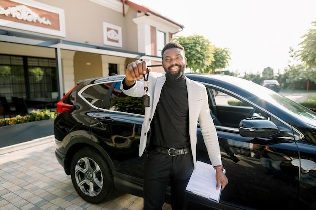 Szczęśliwy amerykanina afrykańskiego pochodzenia mężczyzna pokazuje samochodu klucz stoi blisko nowego czarnego samochodowego skrzyżowania outdoors. młody amerykanina afrykańskiego pochodzenia biznesmen trzyma samochodowego klucz i samochodowej sprzedaży kontrakt