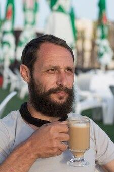 Szczęśliwy amerykański facet ciesząc się pyszną filiżanką kawy. portret przystojny brodaty mężczyzna picia gorącej kawy espresso z mlekiem wygląda na odległość w oświetleniu słońca. mężczyzna trzyma kubek kawy.