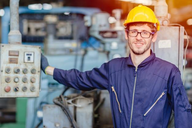 Szczęśliwy amerykański nastoletni pracownik. inżynier ono uśmiecha się dla usługowego utrzymania dylemata maszyny w ciężkim industy z safty kostiumem i hełmem.