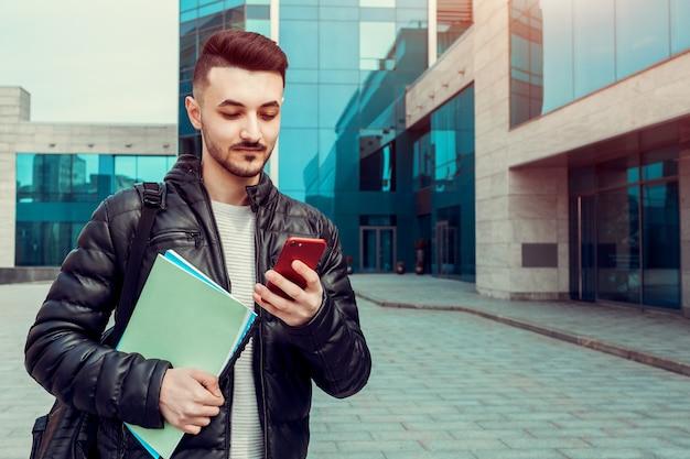 Szczęśliwy arabski student korzystający ze smartfona na zewnątrz