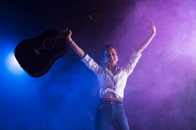 Szczęśliwy artysta trzyma gitarę na scenie