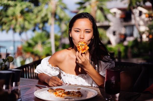 Szczęśliwy asian ładna kobieta głodny o pizzy w słonecznym dniu słońca świetle w restauracji na świeżym powietrzu kobieta korzystających z jedzenia, zabawy na lunch