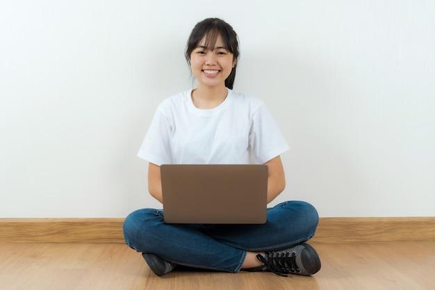 Szczęśliwy asian student siedzi przy użyciu laptopa w domu tło