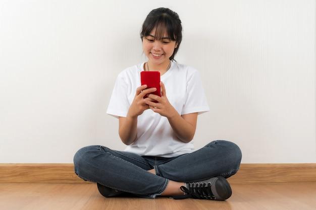Szczęśliwy asian student siedzi przy użyciu telefonu w domu tło