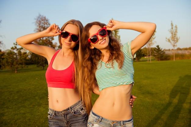 Szczęśliwy atrakcyjne dziewczyny, obejmując się nawzajem i trzymając okulary