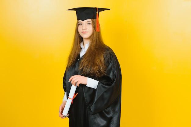 Szczęśliwy atrakcyjny absolwent w stroju mistrza, z dyplomem na żółtej ścianie.
