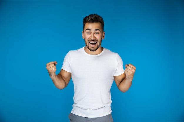 Szczęśliwy atrakcyjny facet na błękitnym tle