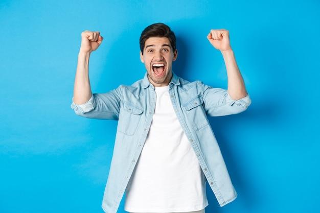 Szczęśliwy, atrakcyjny mężczyzna triumfujący, krzyczący tak i podnoszący ręce do góry, aby świętować zwycięstwo, osiągnąć cel, stojąc na niebieskim tle