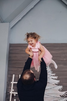 Szczęśliwy, atrakcyjny mężczyzna trzyma się w ramionach i bawi się z małą uroczą dziewczyną w noworocznej atmosferze