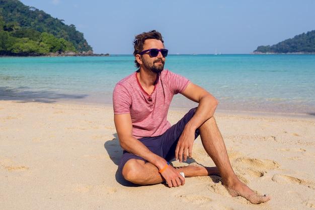 Szczęśliwy atrakcyjny mężczyzna w stylowe okulary przeciwsłoneczne z brodą przy użyciu telefonu komórkowego na plaży