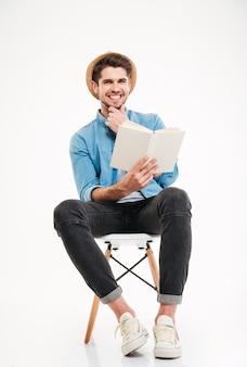 Szczęśliwy atrakcyjny młody człowiek siedzi na krześle i czyta książkę