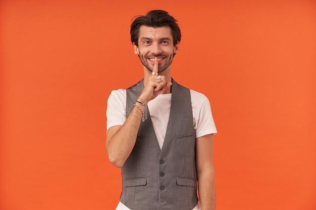 Szczęśliwy atrakcyjny młody człowiek z włosia uśmiecha się i pokazuje znak ciszy na białym tle