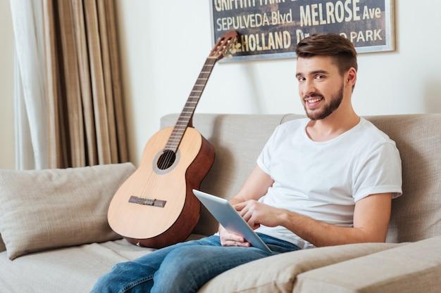 Szczęśliwy atrakcyjny młody mężczyzna siedzi na kanapie i korzysta z tabletu w domu