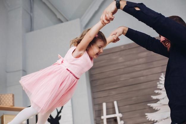 Szczęśliwy atrakcyjny ojciec trzyma w ramionach i bawi się swoim małym uroczym domkiem córki w noworocznej atmosferze