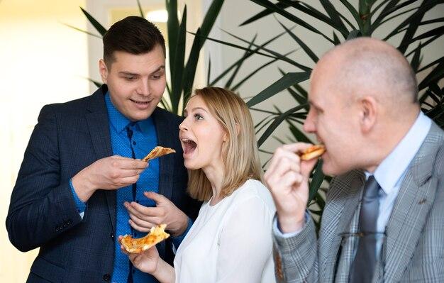 Szczęśliwy atrakcyjny zespół ludzi biznesu jedzenie pizzy w biurze na przerwę obiadową