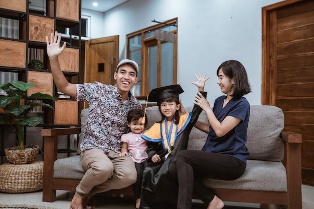 Szczęśliwy azjatycki absolwent rodziny w domu uczeń szkoły podstawowej w domu świętuje home