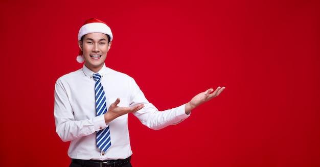 Szczęśliwy azjatycki biznes człowiek ubrany w santa kapelusz prezentujący pomysł otwartej dłoni gest kopiować przestrzeń na białym tle na czerwonej ścianie.