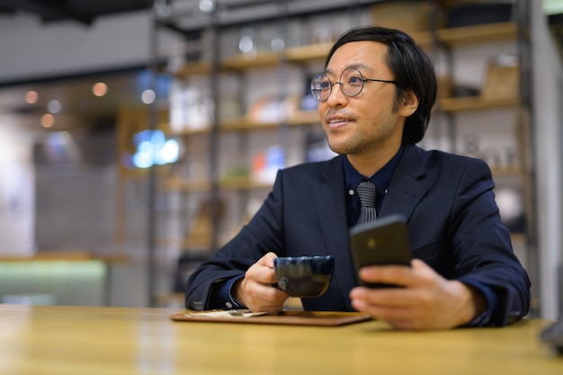 Szczęśliwy azjatycki biznesmen myślenia trzymając filiżankę kawy i ph