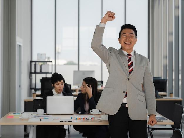 Szczęśliwy azjatycki biznesowy mężczyzna w średnim wieku podniósł rękę w powietrzu świętując sukces przed ludźmi pracującymi w biurze, sukces zespołu biznesowego, koncepcja analizy i strategii