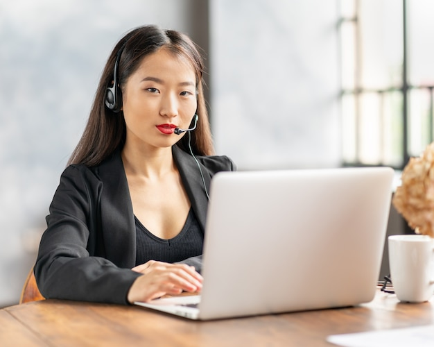 Szczęśliwy azjatycki bizneswoman w mówieniu zestawu słuchawkowego przez połączenie konferencyjne i cha wideo