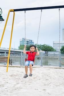 Szczęśliwy azjatycki chłopiec huśta się na placu zabaw w parku