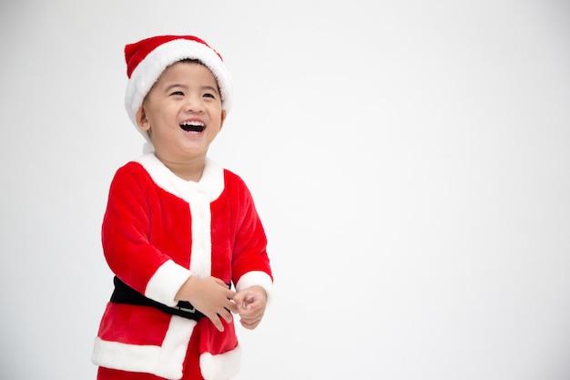 Szczęśliwy azjatycki chłopiec śmiejąc się w świątecznym stroju świętego mikołaja na białym tle na białej ścianie