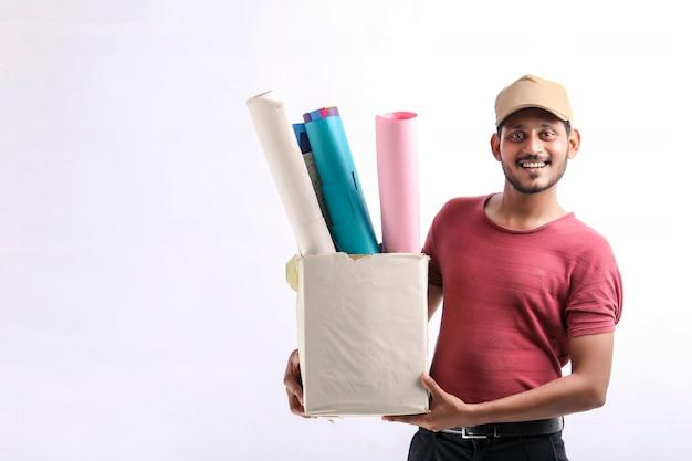 Szczęśliwy azjatycki człowiek w t-shirt i czapka, trzymając pudełko kolor papieru na białym tle nad białym tle, koncepcja usługi dostawy
