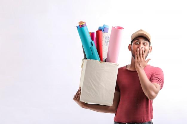 Szczęśliwy azjatycki człowiek w t-shirt i czapkę, trzymając pudełko kolor papieru na białym tle nad białym tle, koncepcja usługi dostawy