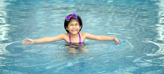 Szczęśliwy azjatycki dzieciak duży uśmiech do gry pływać w basenie z wodą w lecie