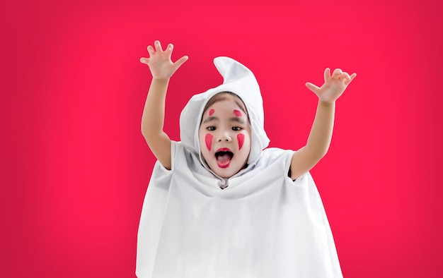 Szczęśliwy azjatycki dzieciak hallooween w kostium ducha na czerwono ze ścieżką przycinającą