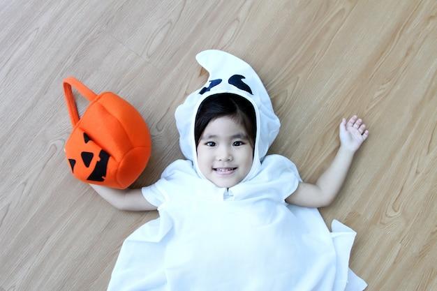 Szczęśliwy azjatycki dzieciak hallooween w kostium ducha na czerwono